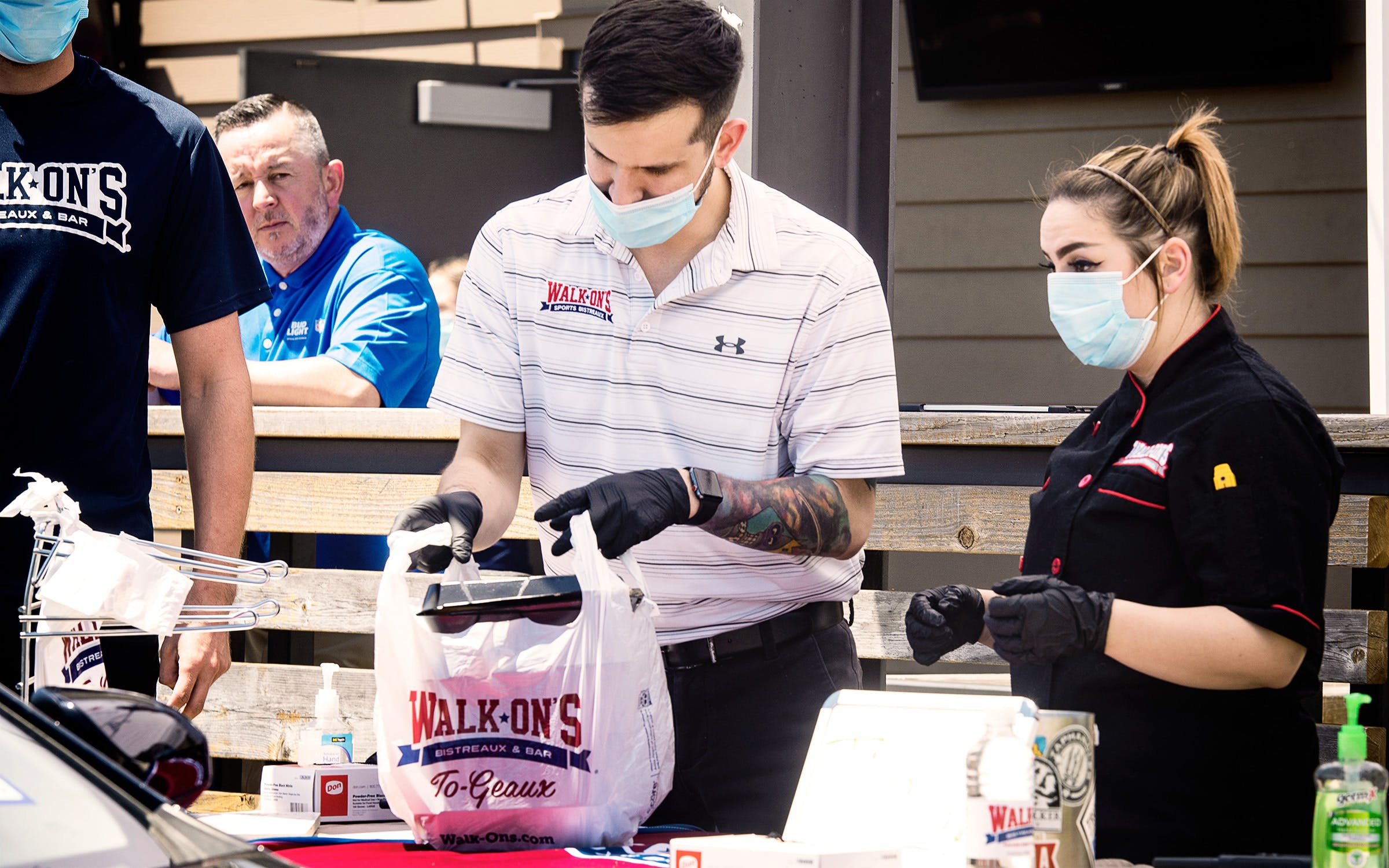 Walk-On's Sports Bistreaux general manager Fernando Guzman and executive kitchen manager Presley Parker bag meals to hand out during the restaurant's Furlough Kitchen by Walk-On's event in Tyler on April 30, 2020.