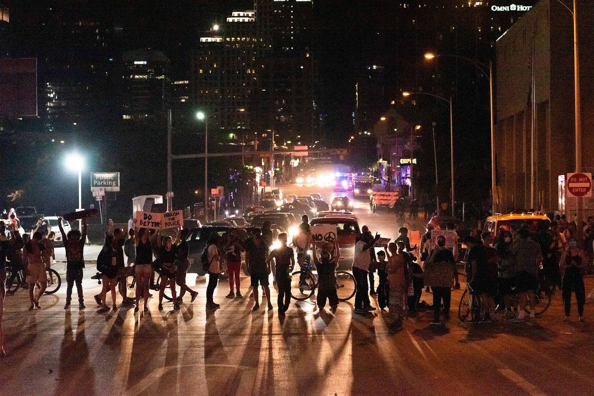 Protesters kneel while blocking the intersection of 7th Street and I-35 in front of police headquarters in Austin on May 30, 2020.