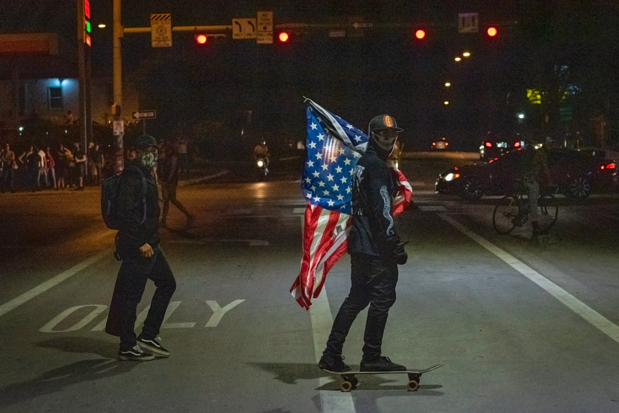 A protester rides a skateboard with an American flag under I-35 at 7th Street in front of police headquarters in Austin on May 30, 2020.