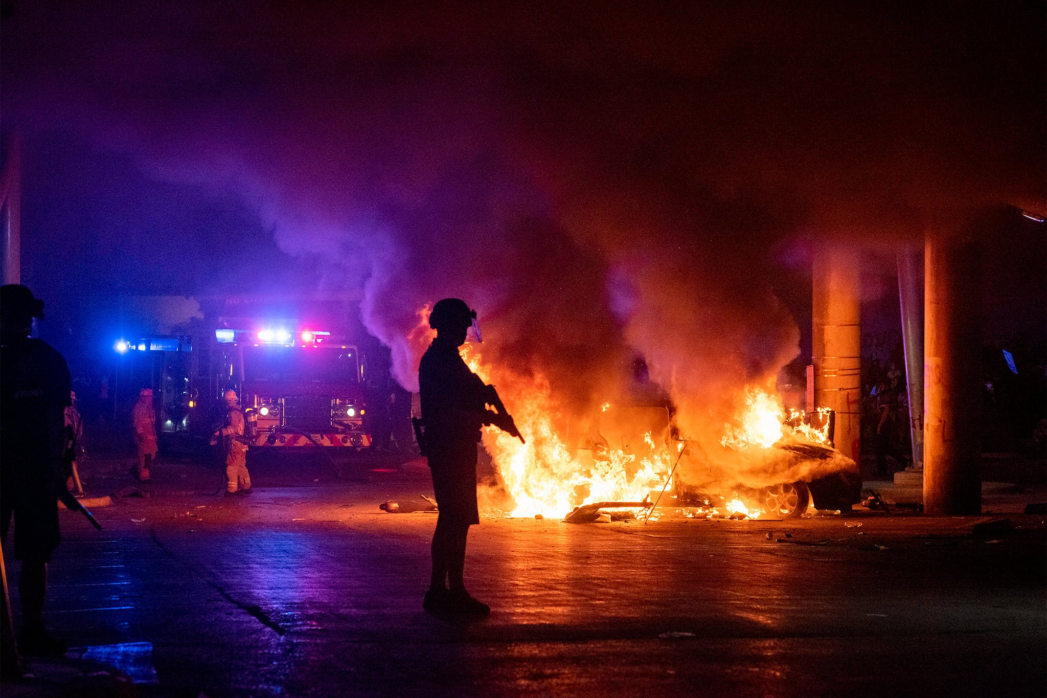 Officer protects the perimeter of a burning car under I-35 so firefighters can put it out during protests in Austin on May 30, 2020.