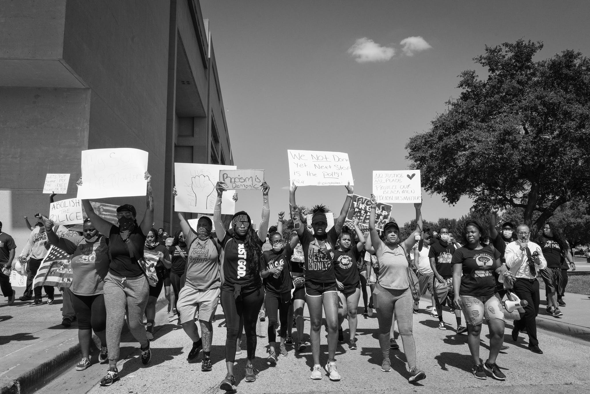 """A crowd chants """"I can't breathe!"""" as they march past Dallas City Hall on June 3, 2020."""