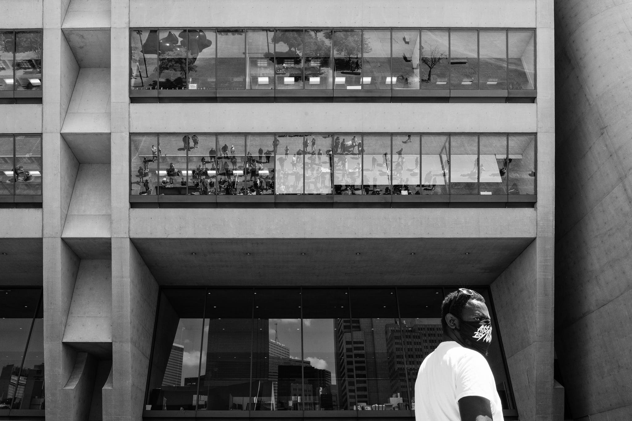 A man stands elevated above the crowd at Dallas City Hall with the reflection of the protest below on June 3, 2020.