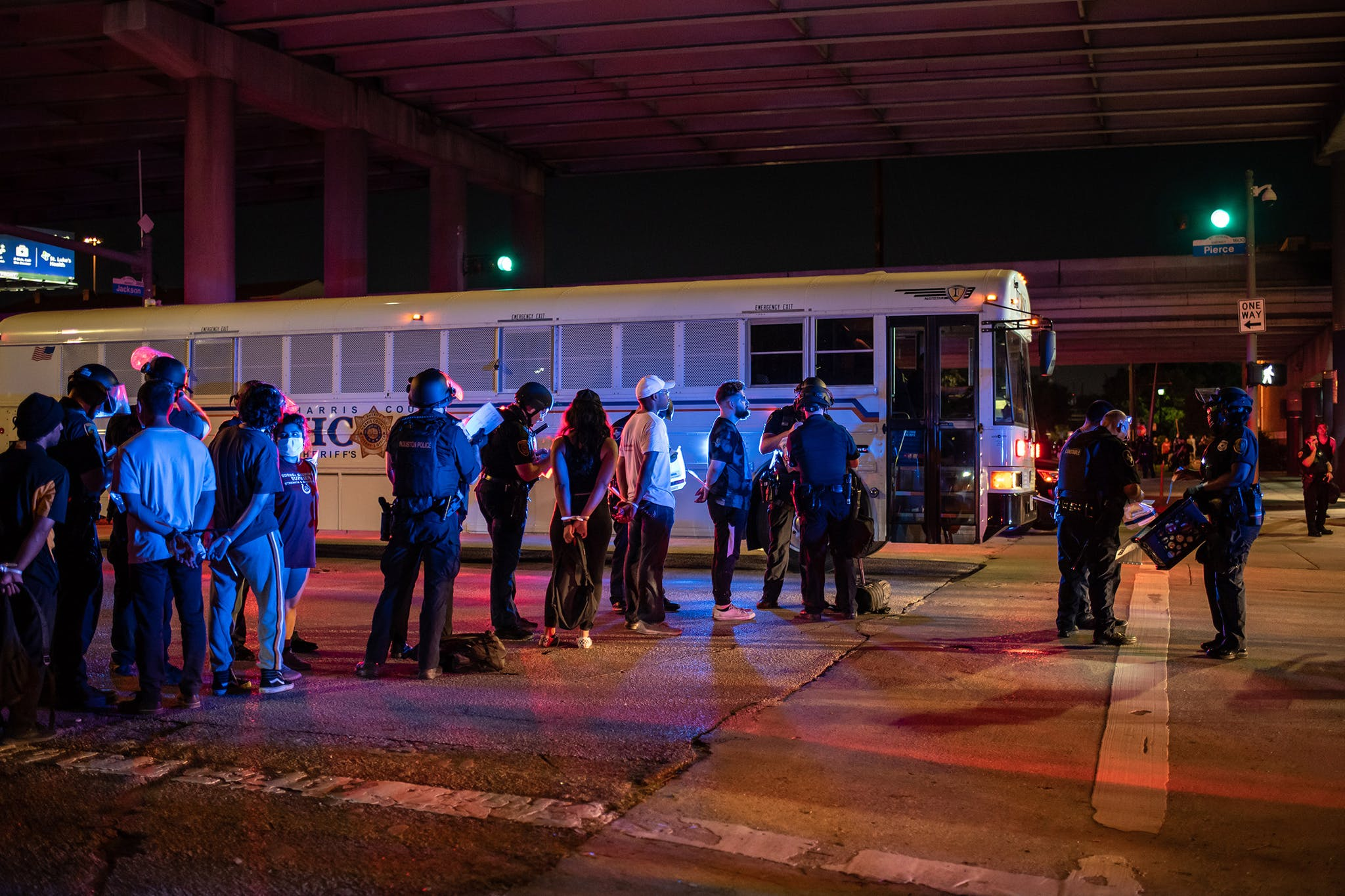 A group of people being placed under arrest stand by a Harris County Jail bus after protesters were apprehended in a fenced in area in Houston, on June 2, 2020.