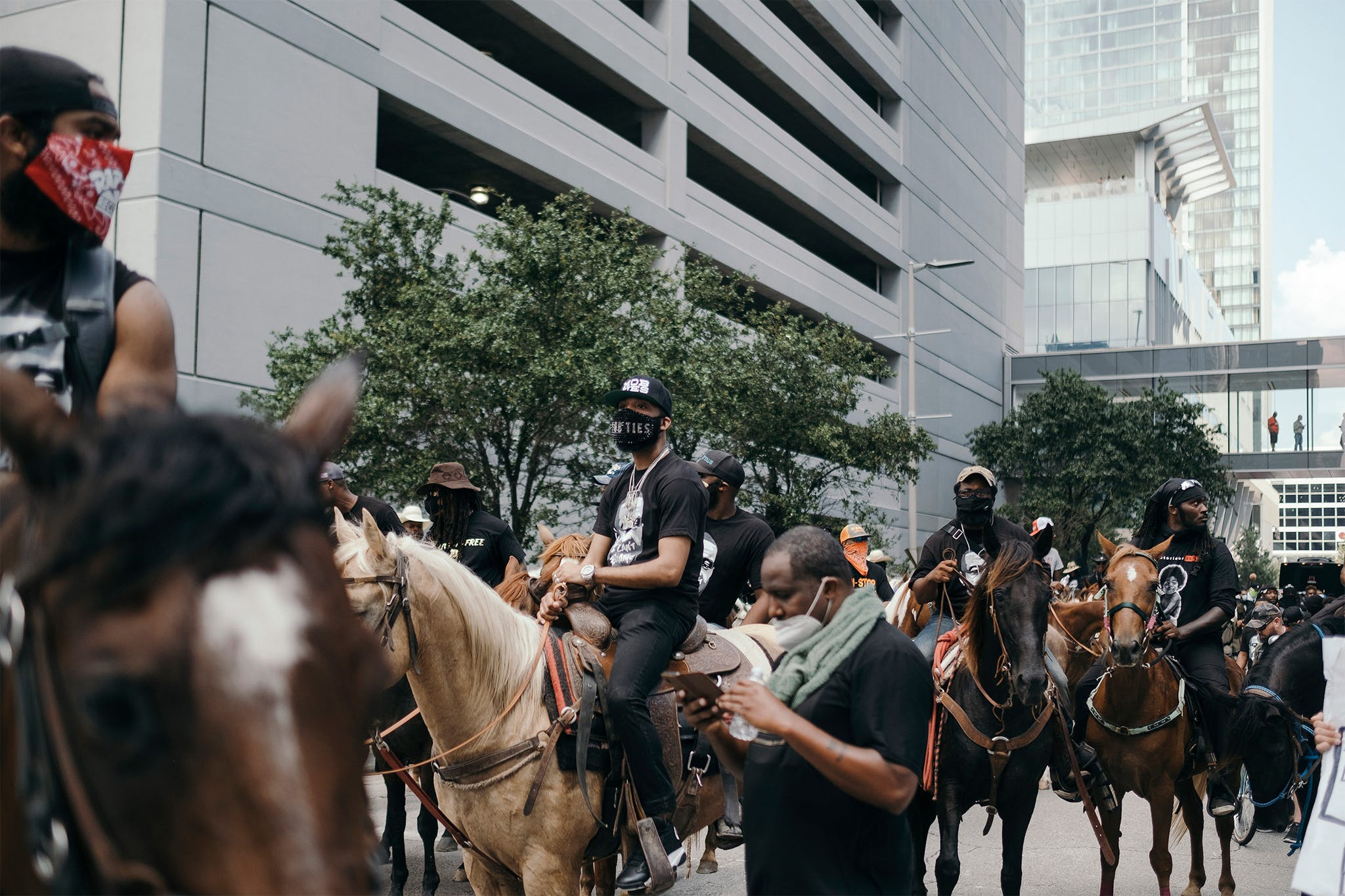 J Prince Jr, center, prepares to ride his horse down Walker street during a march to honor the memory of George Floyd in downtown Houston on June 2, 2020.