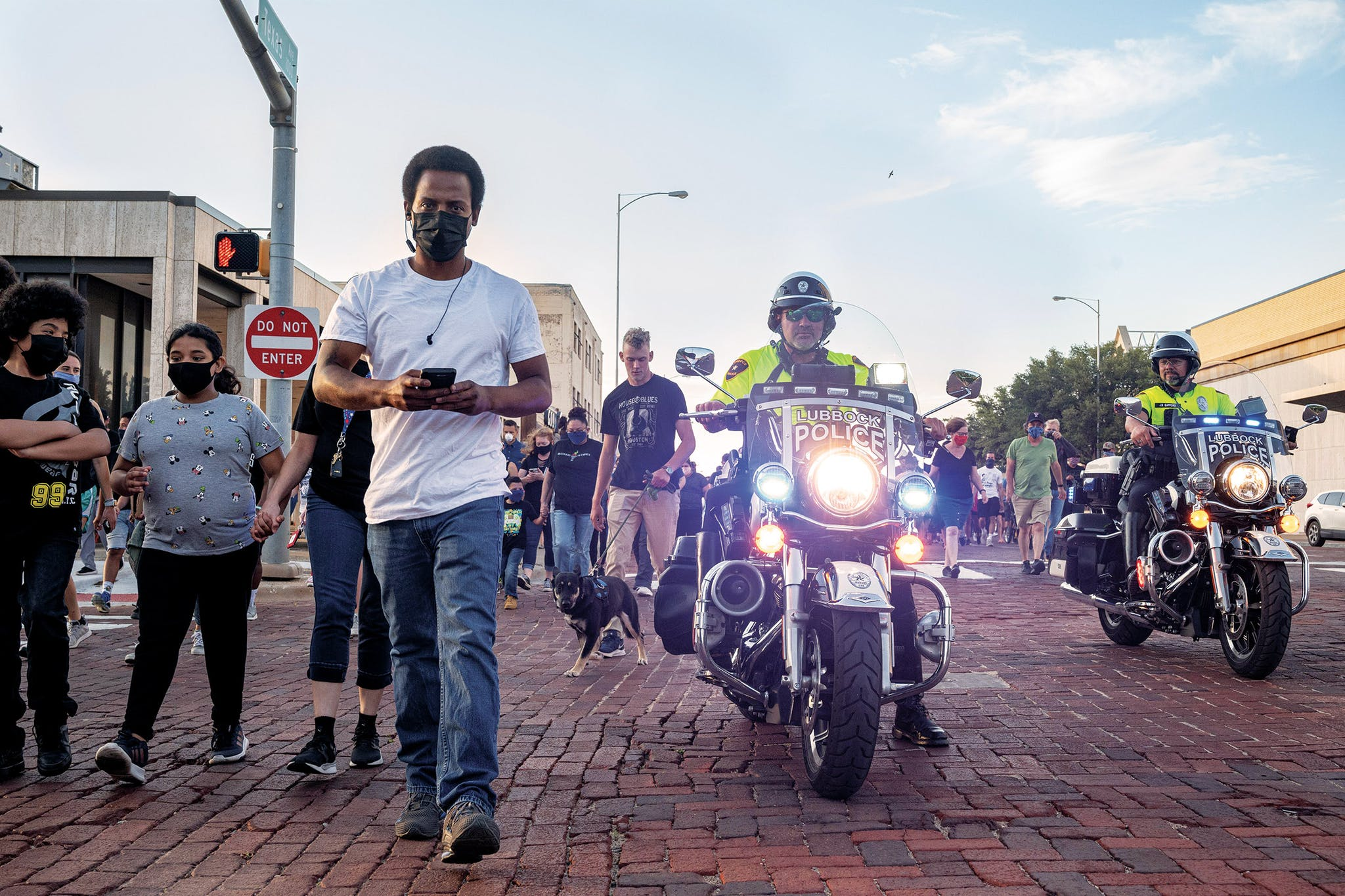 Participants in the 100 Black Men of West Texas solidarity walk are escorted by police officers at 8 p.m. in Lubbock on June 1, 2020.