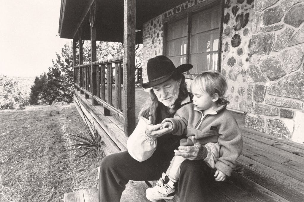 Willie with his son Lukas Autry, two, chatting on the front steps of his cabin.