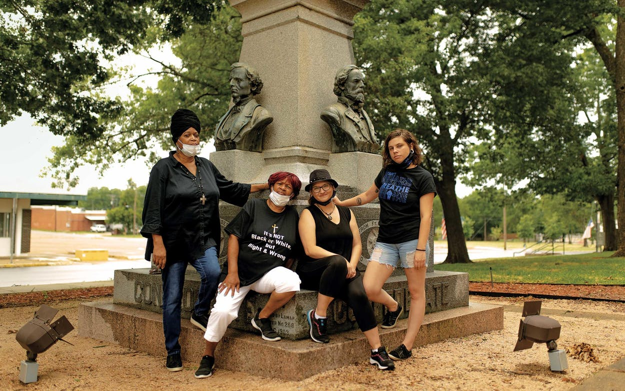 From left, Brenda Cherry, Carolyn Williams, Latrel Lacy, and Taisley Scroggin in front of the Confederate statue at the Lamar County Courthouse on July 4, 2020. They are requesting that the monument be moved.