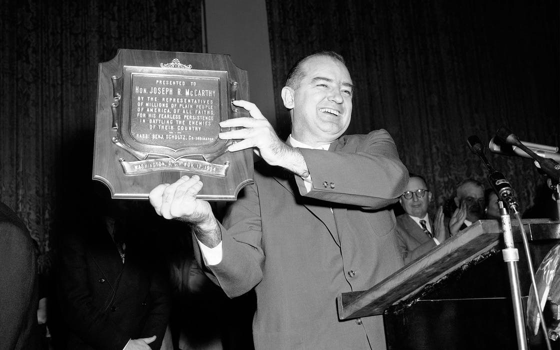 "Sen. Joseph McCarthy (R-Wis.), holds aloft a plaque, misdated, which was presented to him in Washington, D.C., Nov. 11, 1954 at the meeting staged to protest his censure hearing by the Senate. More than 3,000 well-wishers gathered at a Constitution Hall rally to honor the senator. The plaque was presented to McCarthy for his ""fearless persistence"" in battling the enemies of America."