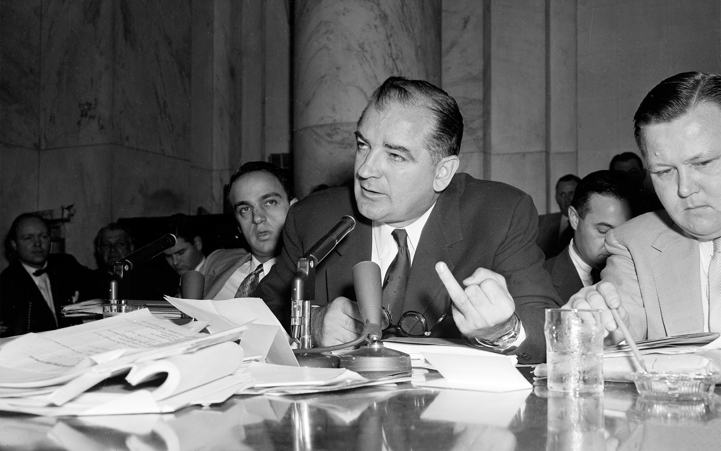 Sen. Joseph McCarthy gestures as he directs a question to Army Secretary Robert Stevens during the afternoon session of the hearings into his differences with high Pentagon officials, in Washington, D.C., on April 28, 1954. McCarthy's aide, Roy Cohn, is at left.