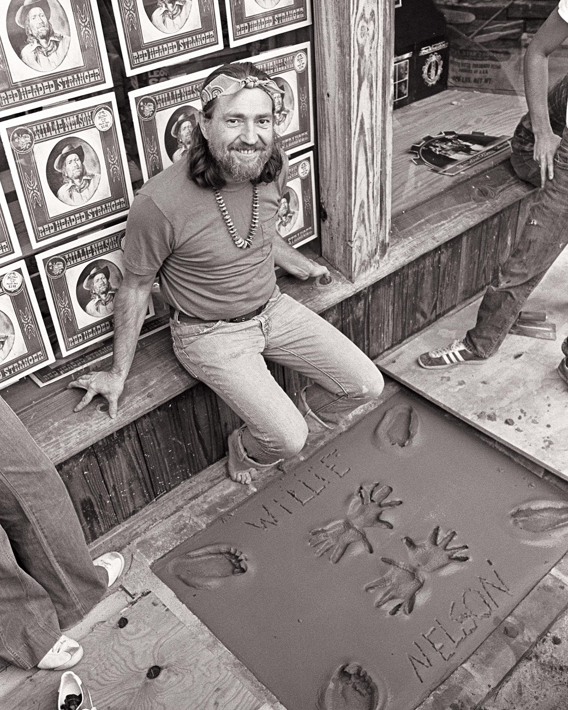 Willie casting his footprints and handprints during an in-store appearance promoting Red Headed Stranger at Peaches Records, in Atlanta, on October 28, 1975.