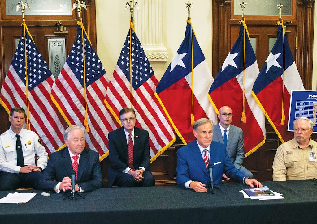 State officials surround Texas governor Greg Abbott (third from right) as he announces the reopening of more Texas businesses at a press conference at the Capitol in Austin on Monday, May 18, 2020.