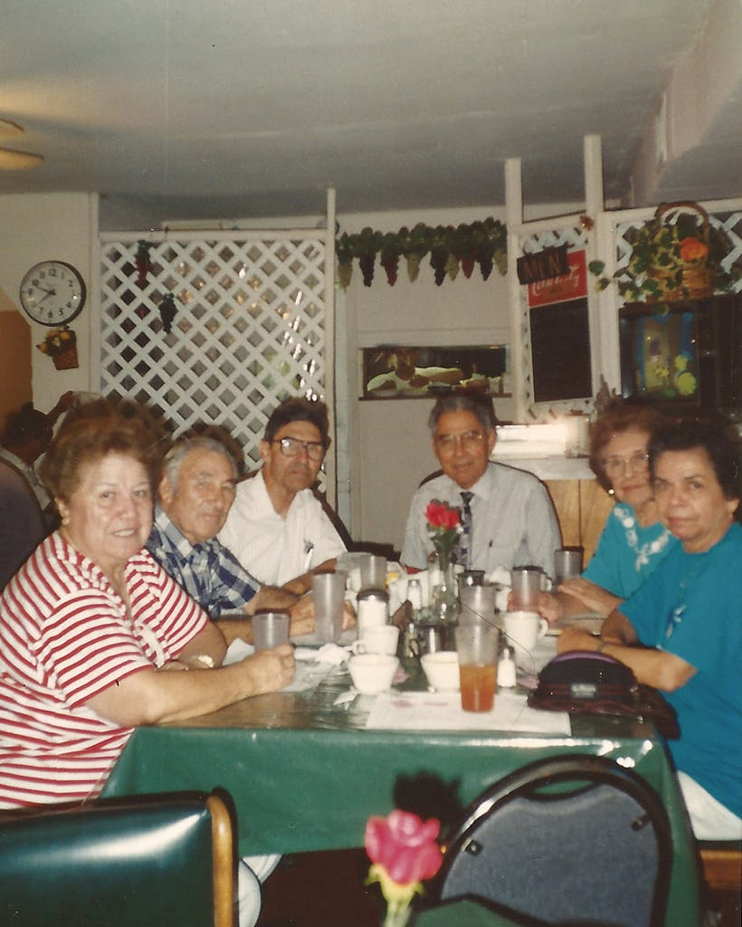 The author's father (head of the table) and aunts and uncles together at a restaurant in Brownsville in 1996.