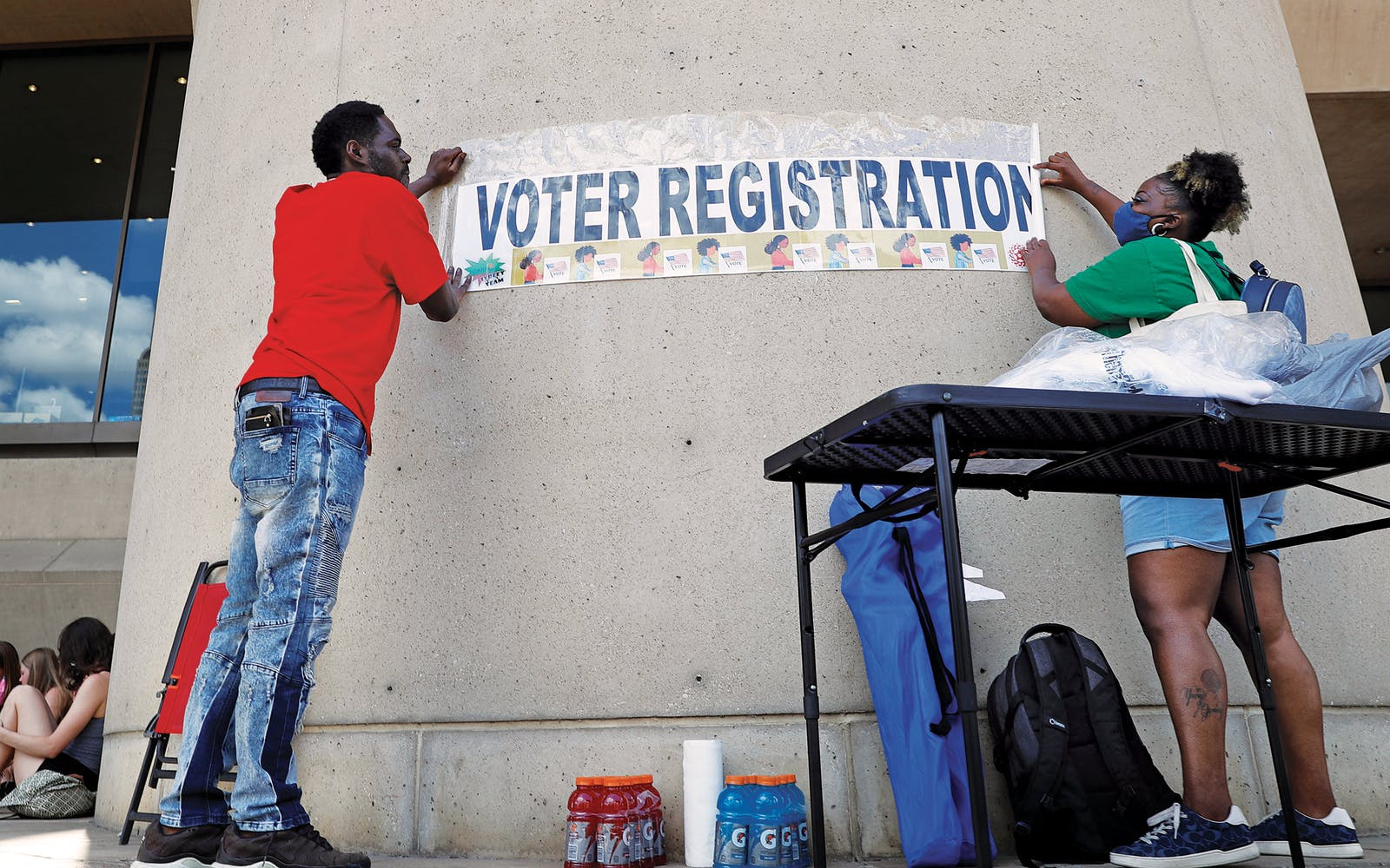Aetry Jones, left, and Caerry Rigbon tape up a voter registration sign on Dallas City Hall before a Juneteenth 2020 celebration and protest against police brutality in Dallas, on June 19, 2020.