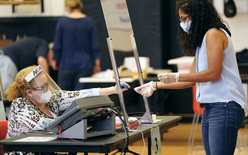 Harris County election clerk Nora Martinez, left, helps a voter while taking COVID-19 precautions during early voting for the Texas primary runoffs in Houston on June 29, 2020.