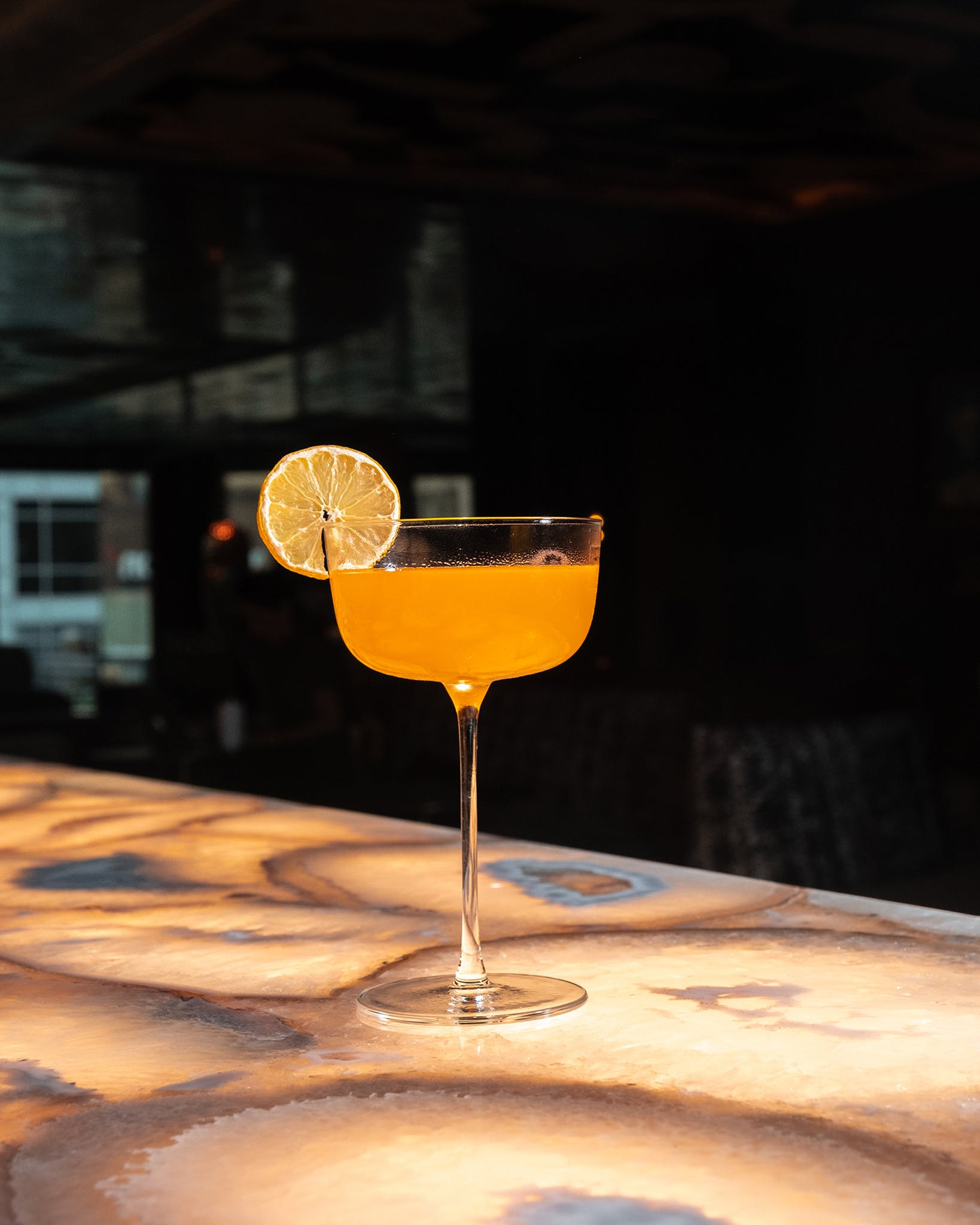 The bar counter, an agate wonder from Italian stone dealer Antolini, is almost too pretty to cover up with cocktails like this signature daiquiri, which is made with rum, Aperol, lime, and mango.