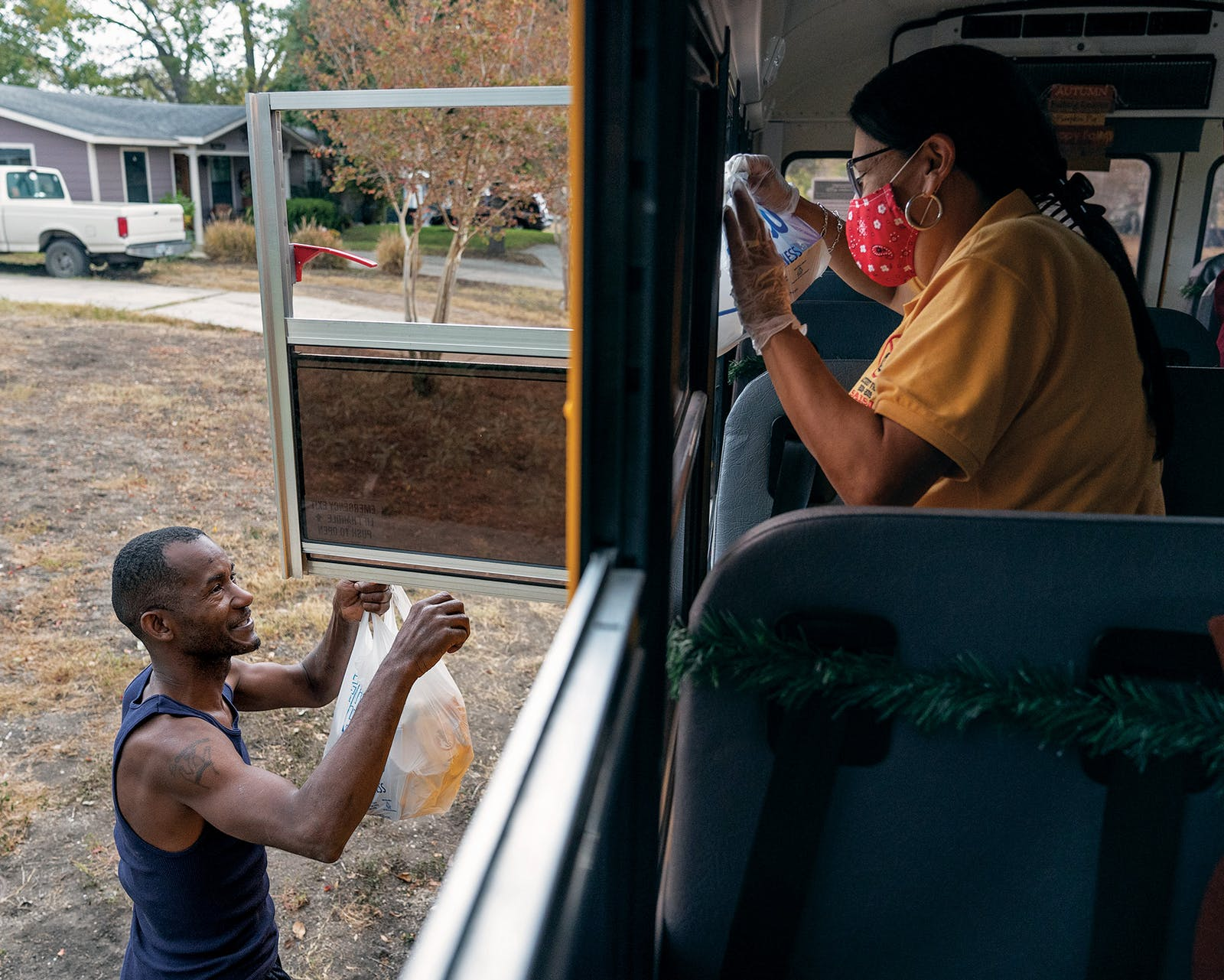 Richards passes bags of food to Lawrence Walker, 45, a parent of four children on Richardson's bus route.