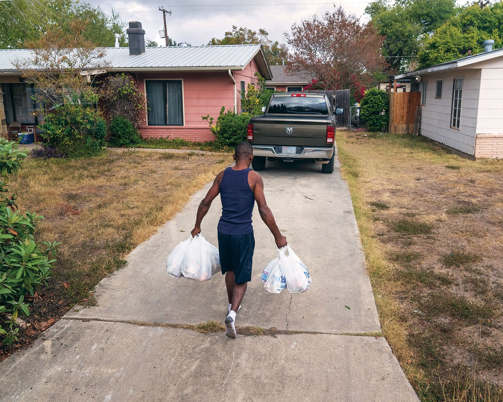 Lawrence Walker carries groceries back to his home after picking up food from the school bus.