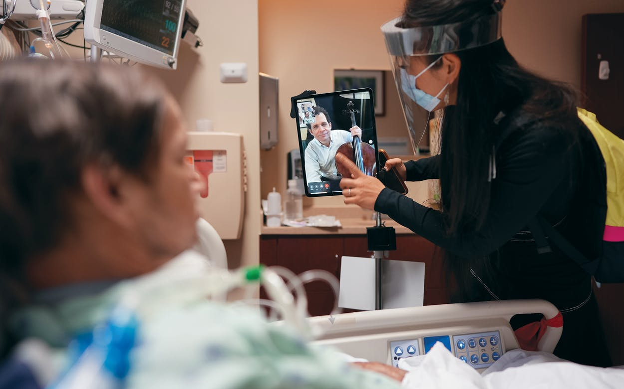 Dr. Mei Rui sets up the iPad for cellist Brinton Averil Smith to play a virtual performance for patient Ron Friedel at Houston Methodist.