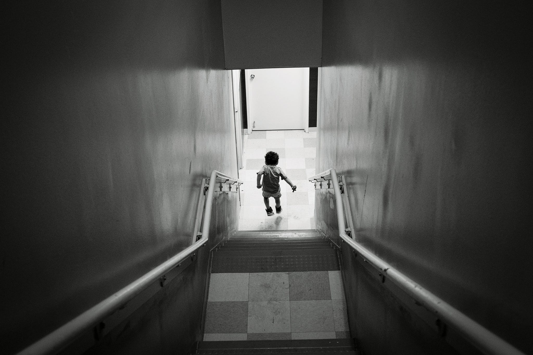 A young boy jumps down a stairwell on the way to the shelter's cafeteria after lunch is announced over the intercom.