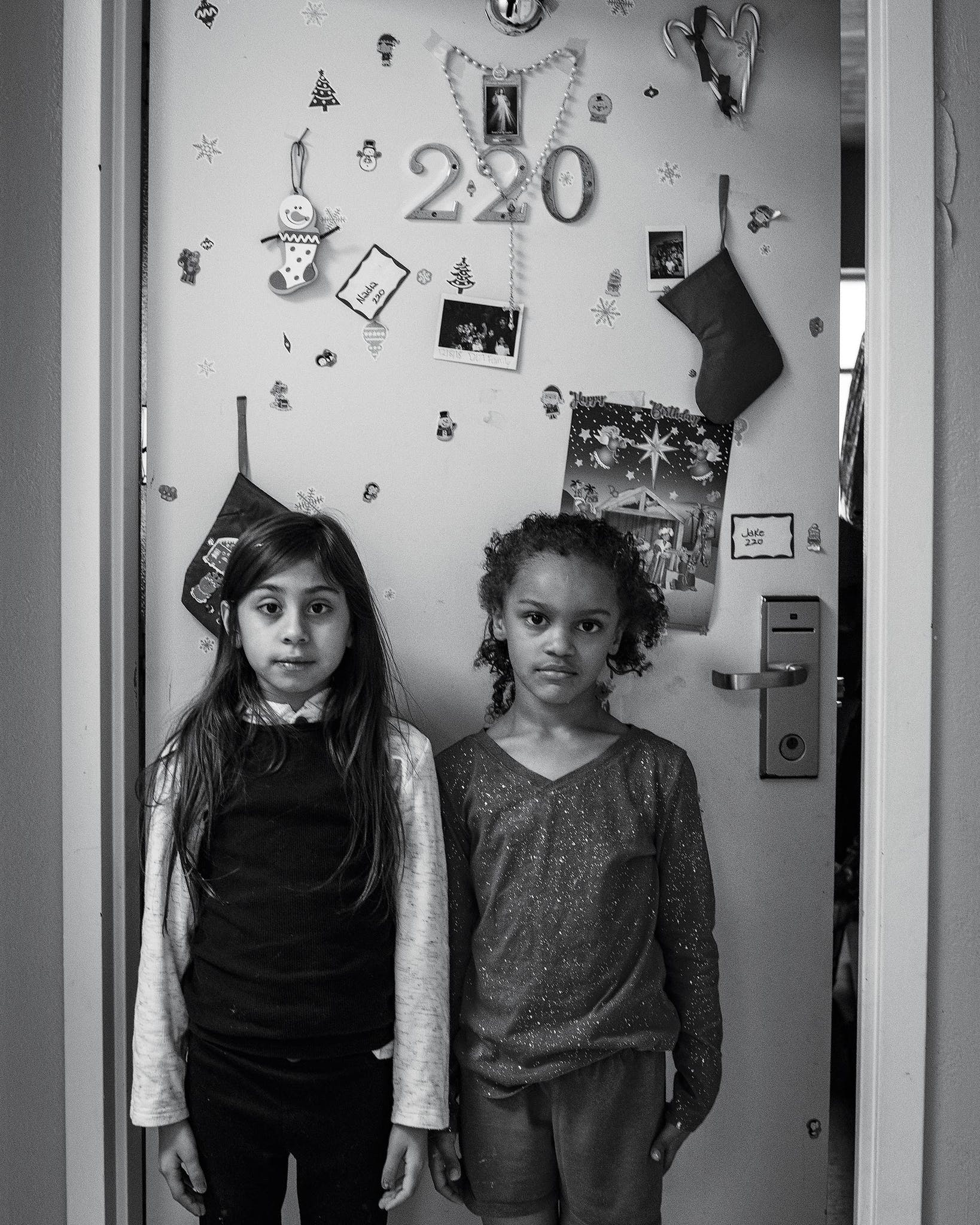 Nadia De La Torre, 9, stands outside her family's room with her friend Skye Griffin, 8, who lives next door.