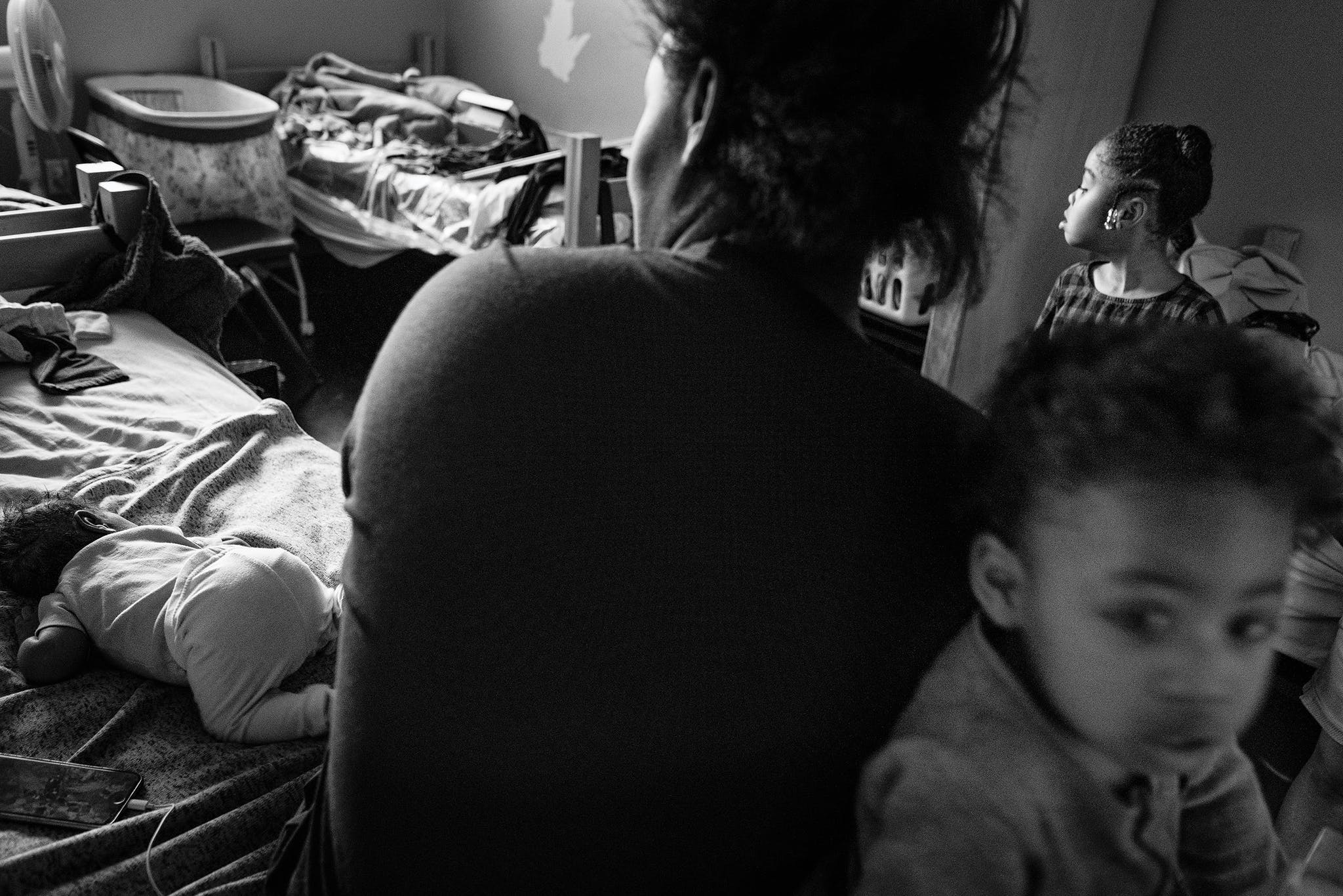 Whitney Bryant sits in her room at a shelter with three of her children—Kadyn, 6, Kasir, 2, and Khali, an infant—in February 2020.
