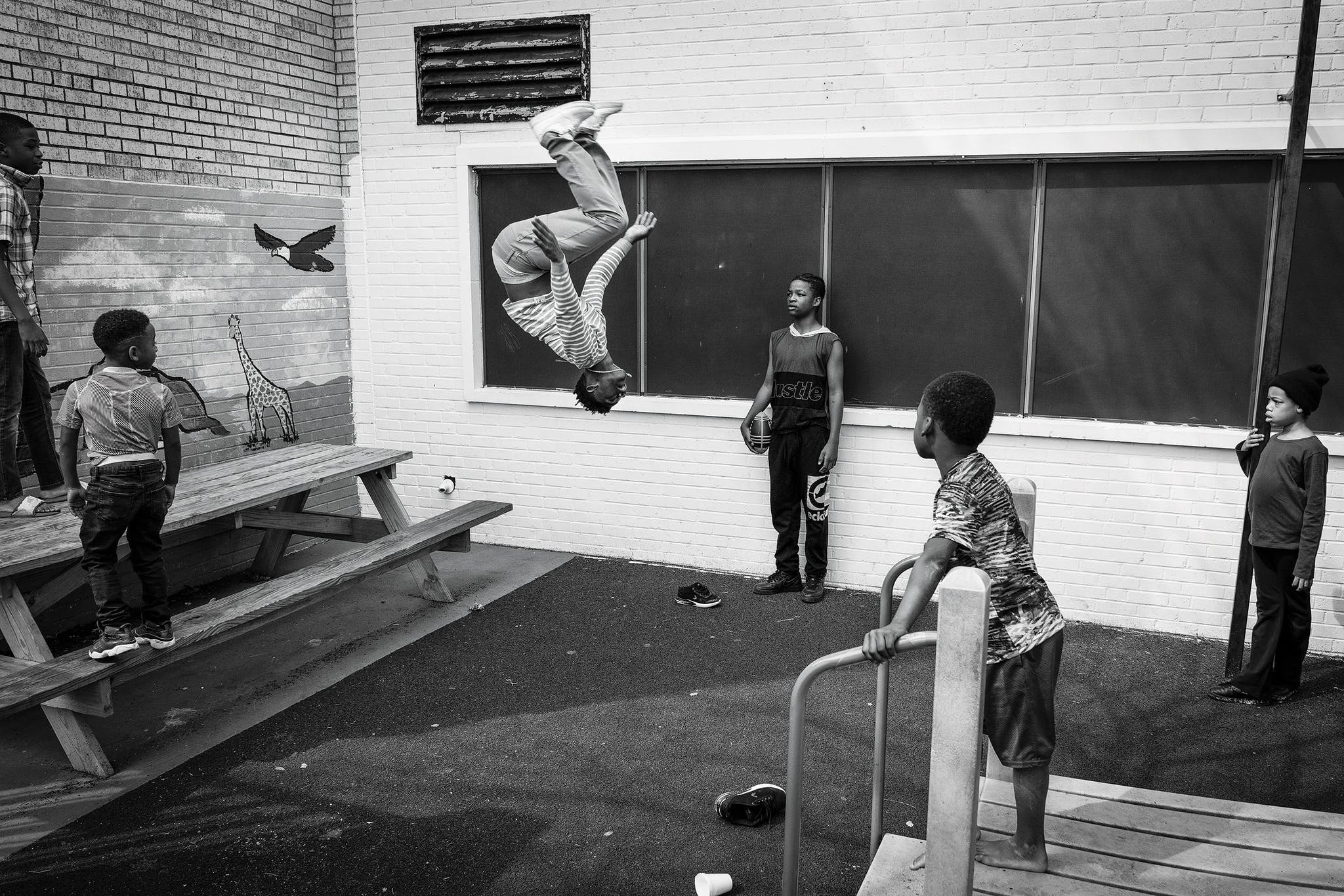 Dre, seventeen, does a backflip on the playground of Family Gateway's shelter in February 2020.