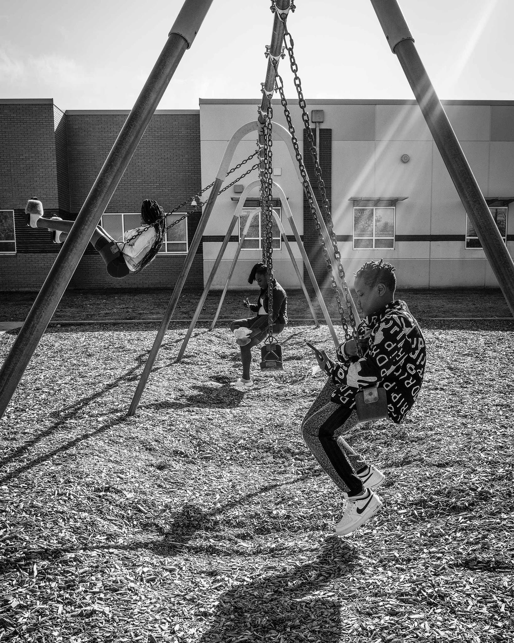 Johnson's son Cavier, eleven, swings on a playground behind his elementary school, across the street from the Dallas apartment complex where he lives.