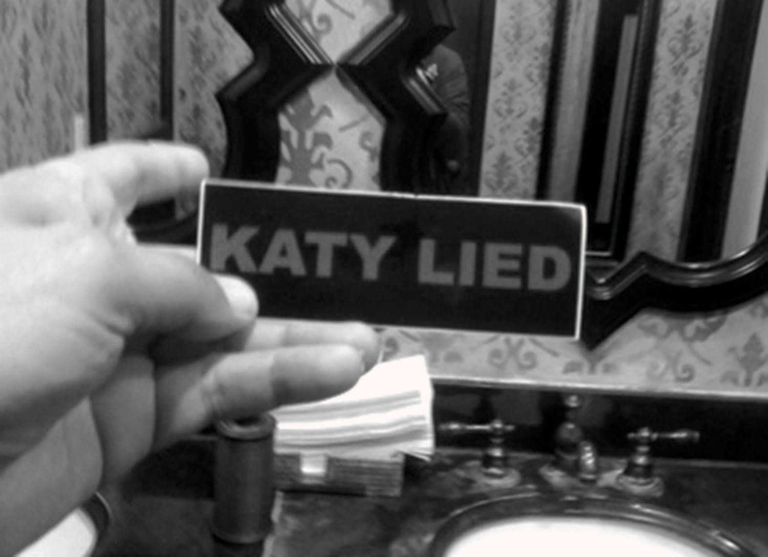 "A ""KATY LIED"" sticker in the restroom of Century Bar & Grill, in Alpine's Holland Hotel."