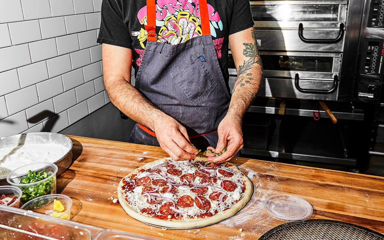The tomato, mozzarella, pineapple, speck, and fresh jalapeño pizza at Tiny Champions, in Houston.