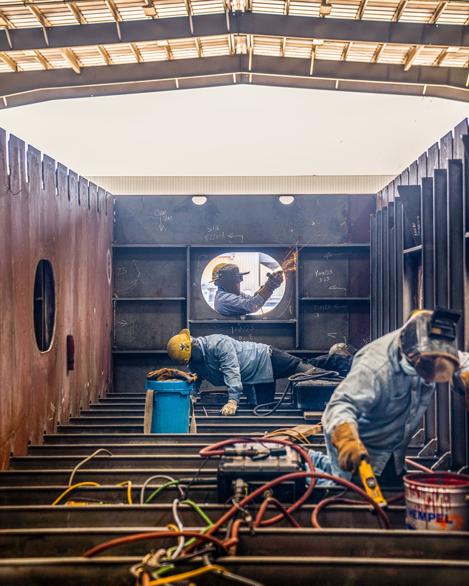 """Workers welding steel on one of the sections of the Charybdis wind-turbine-installation vessel – a section known as a """"sub-block."""