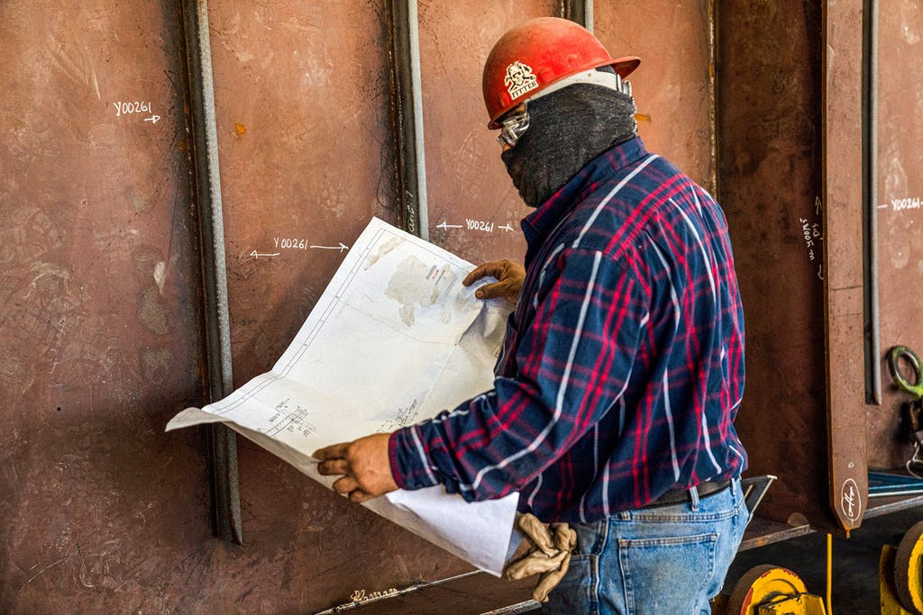 A worker standing by a section of Charybdis reading project drawings for the construction of the ship.