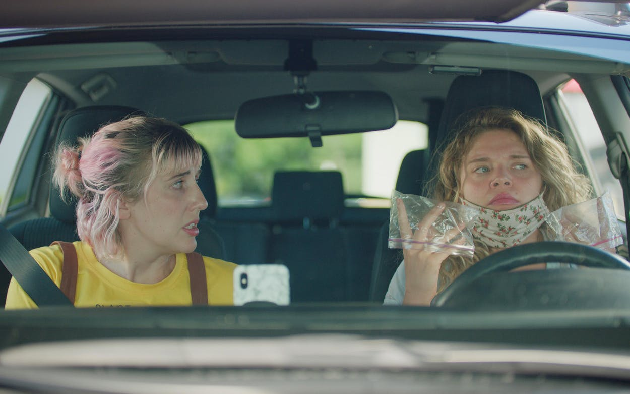 Blake (Mallory Everton) steels herself to exit the car during a pandemic and handle a sticky gas pump, armed with nothing but snack-size sandwich bags for gloves in Recovery.
