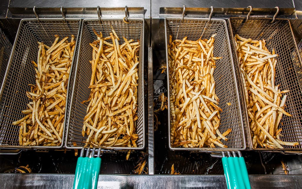 Batches of fries, fresh out of the oil.
