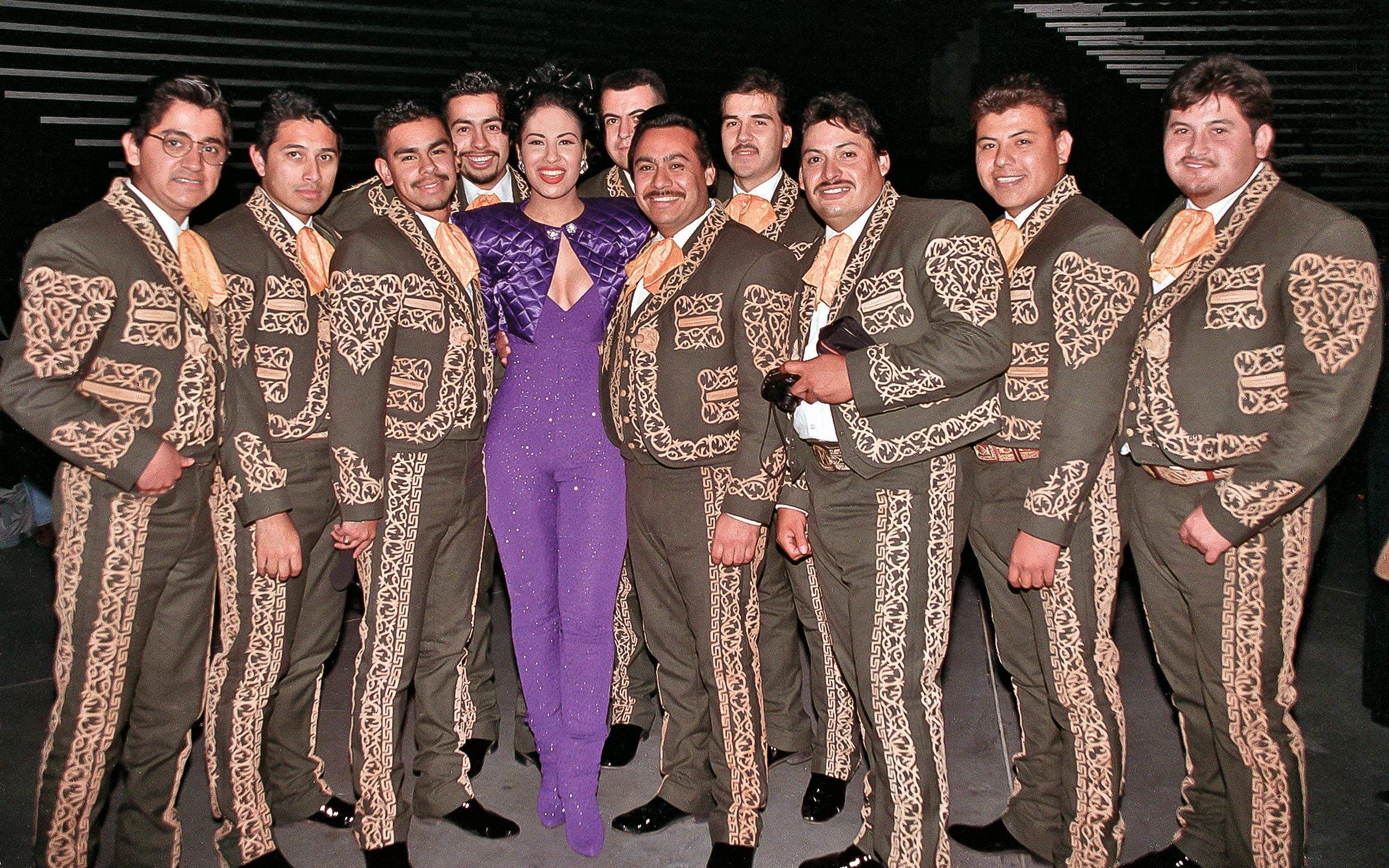 Selena, in a purple jumpsuit and quilted bolero jacket, with the mariachi Los Caporales, at the Tejano Music Awards in San Antonio, on February 11, 1995