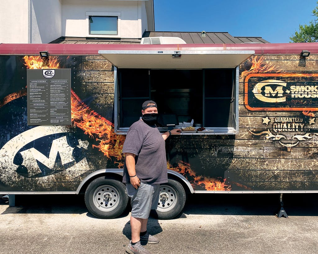 Cade Mercer in front of the CM Smokehouse trailer in Austin.