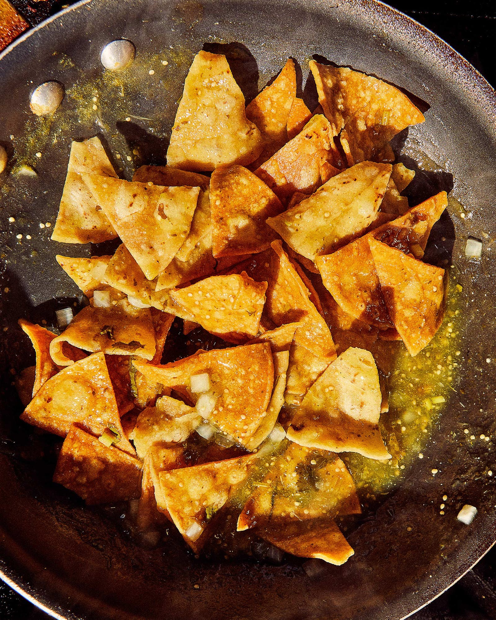Tortilla chips and salsa are prepped for chilaquiles in a pan at Tía Dora's Bakery.