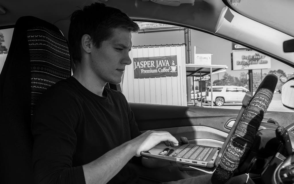 Gus Peters working in his car outside Jasper Java