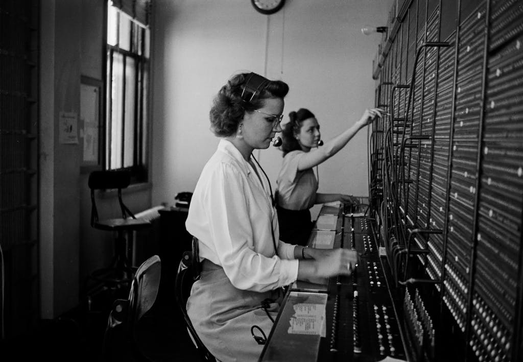 Two unidentified Bell telephone operators work at a large switchboard in the 1940s.