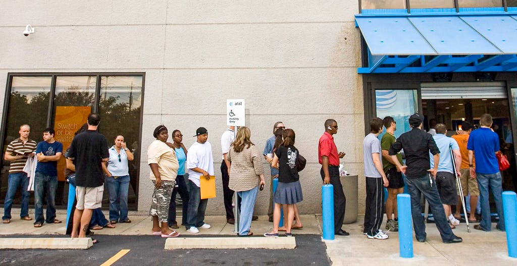 Customers wait in line to buy the Apple iPhone at the AT&T cellular store June 29, 2007 in Houston.