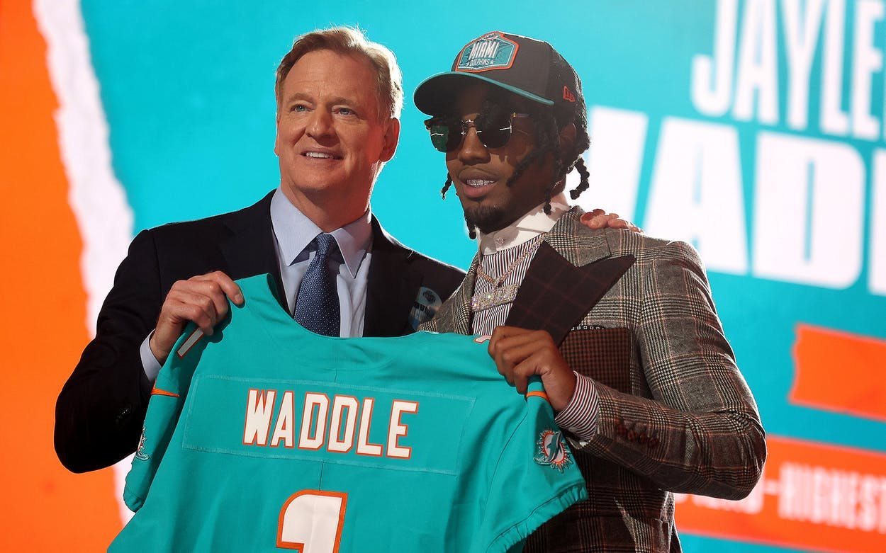 Jaylen Waddle poses with NFL Commissioner Roger Goodell onstage after being selected with the sixth pick by the Miami Dolphins during round one of the 2021 NFL Draft at the Great Lakes Science Center on April 29, 2021 in Cleveland, Ohio.