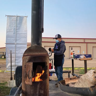 Andres Reyes from Rankin High School manages his team's fire at the Texas State High School BBQ Championship on April 23, 2021.
