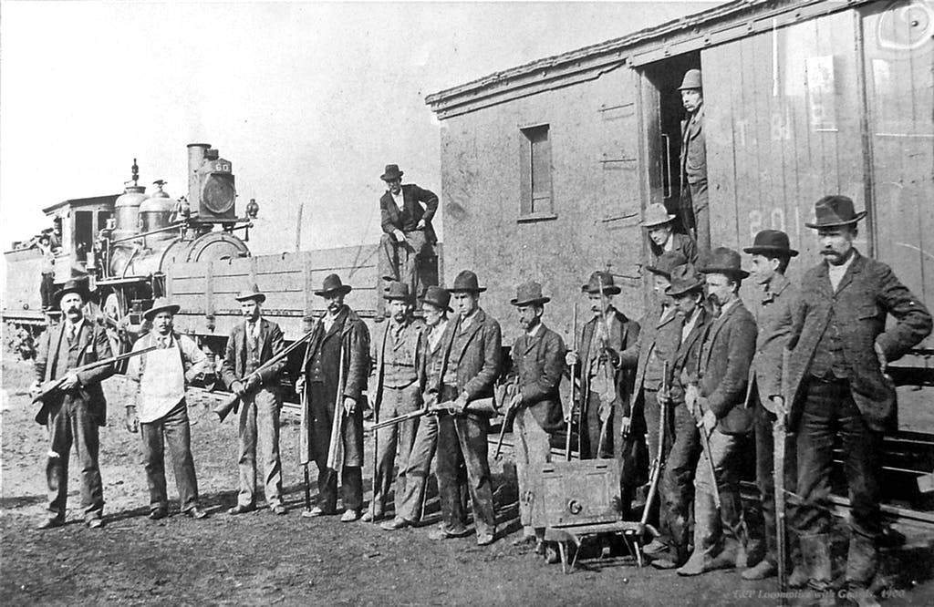 Reeves stands in the doorway of boxcar on the MKT Railroad line, guarding a shipment with fellow lawmen, near Muskogee, I.T. circa 1900.