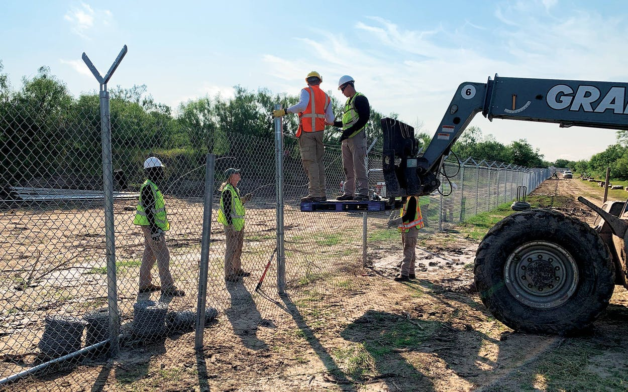 Texas National Guardsmen add razor wire to the top of the fence, just west of Del Rio on July 21, 2021.