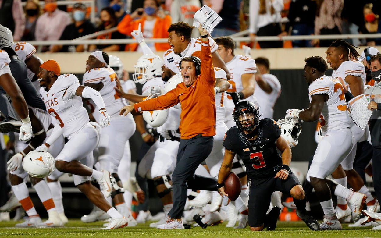 The Texas Longhorns celebrate their upset victory as quarterback Spencer Sanders #3 of the Oklahoma State Cowboys reacts after getting taken down on the final play in overtime against the Texas Longhorns on October 31, 2020.