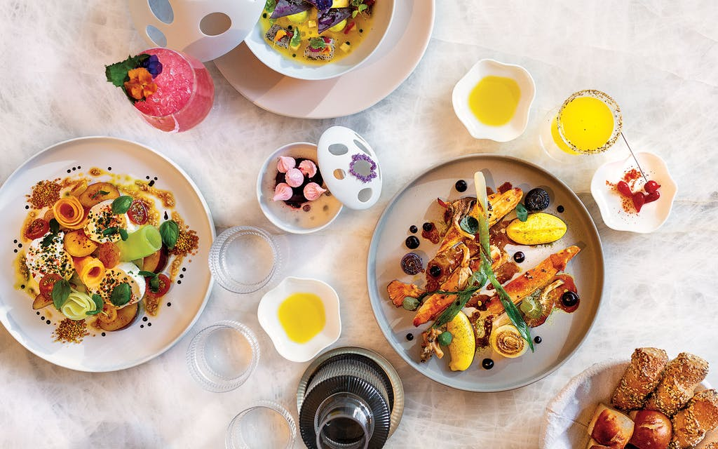 A colorful spread, including (clockwise from top) the King Kampachi crudo, grilled chicken with corn mousse, and burrata with heirloom melon.