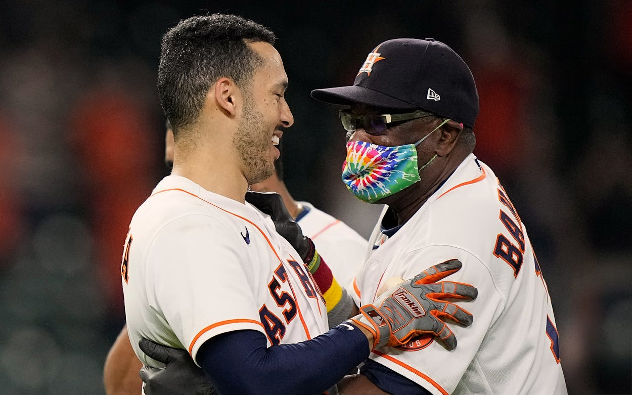 Houston Astros' Carlos Correa, left, celebrates with manager Dusty Baker Jr. after hitting a game-winning RBI ground-rule double against the Seattle Mariners during the 10th inning of a baseball game Tuesday, Sept. 7, 2021, in Houston.