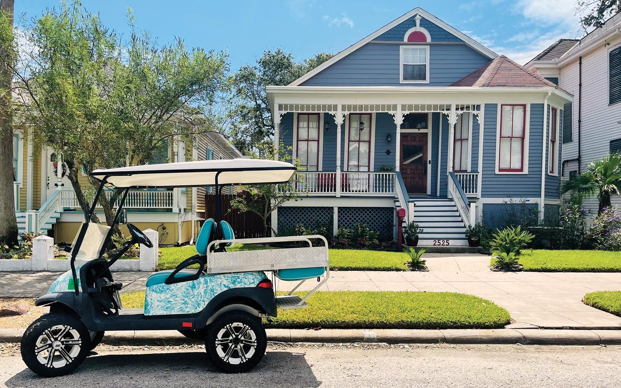 A golf cart parked outside of a historic rental home in Galveston.