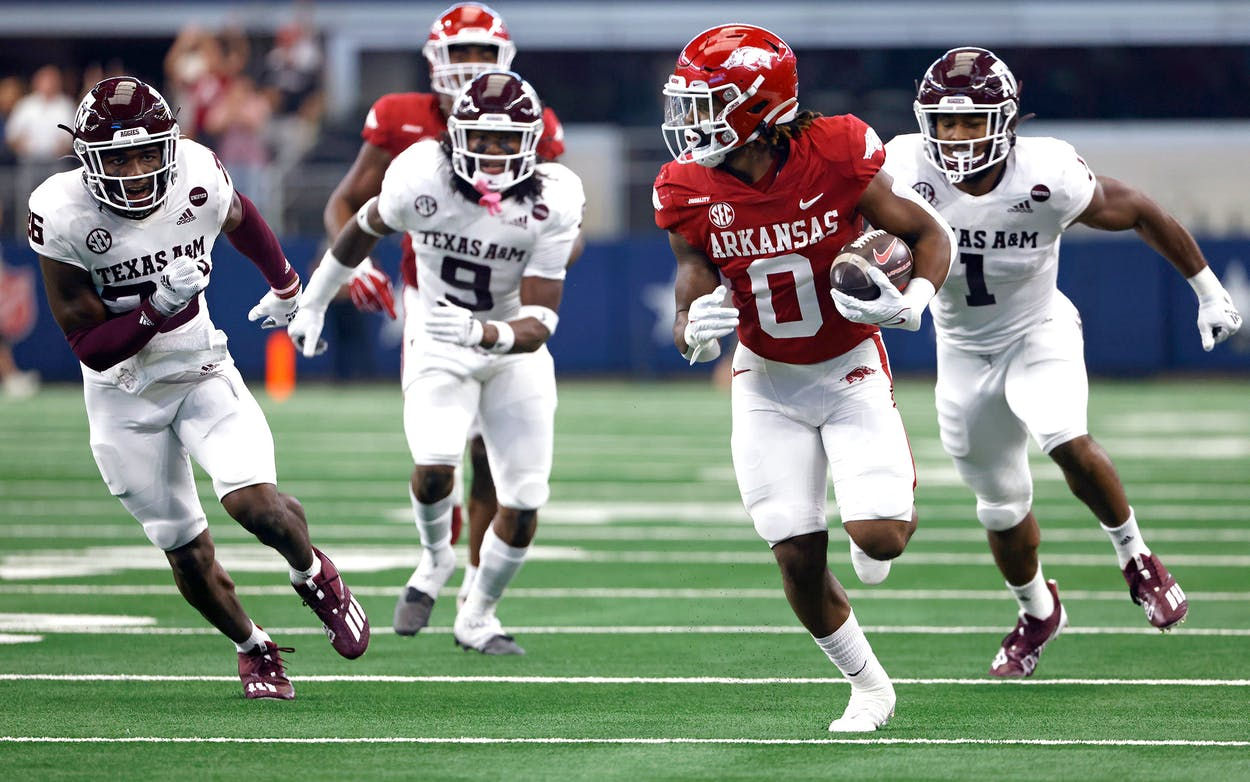 AJ Green #0 of the Arkansas Razorbacks runs past a host of Texas A&M Aggies defenders before scoring a touchdown in the first half of the Southwest Classic at AT&T Stadium on September 25, 2021 in Arlington, Texas.