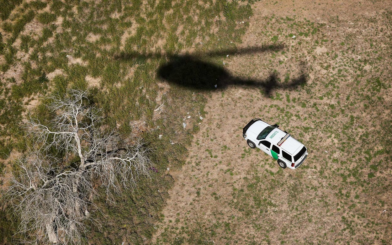 The shadow of a helicopter from U.S. Office of Air and Marine passes a U.S. Border Patrol vehicle as agents search for undocumented immigrants in 2014 in Falfurrias.