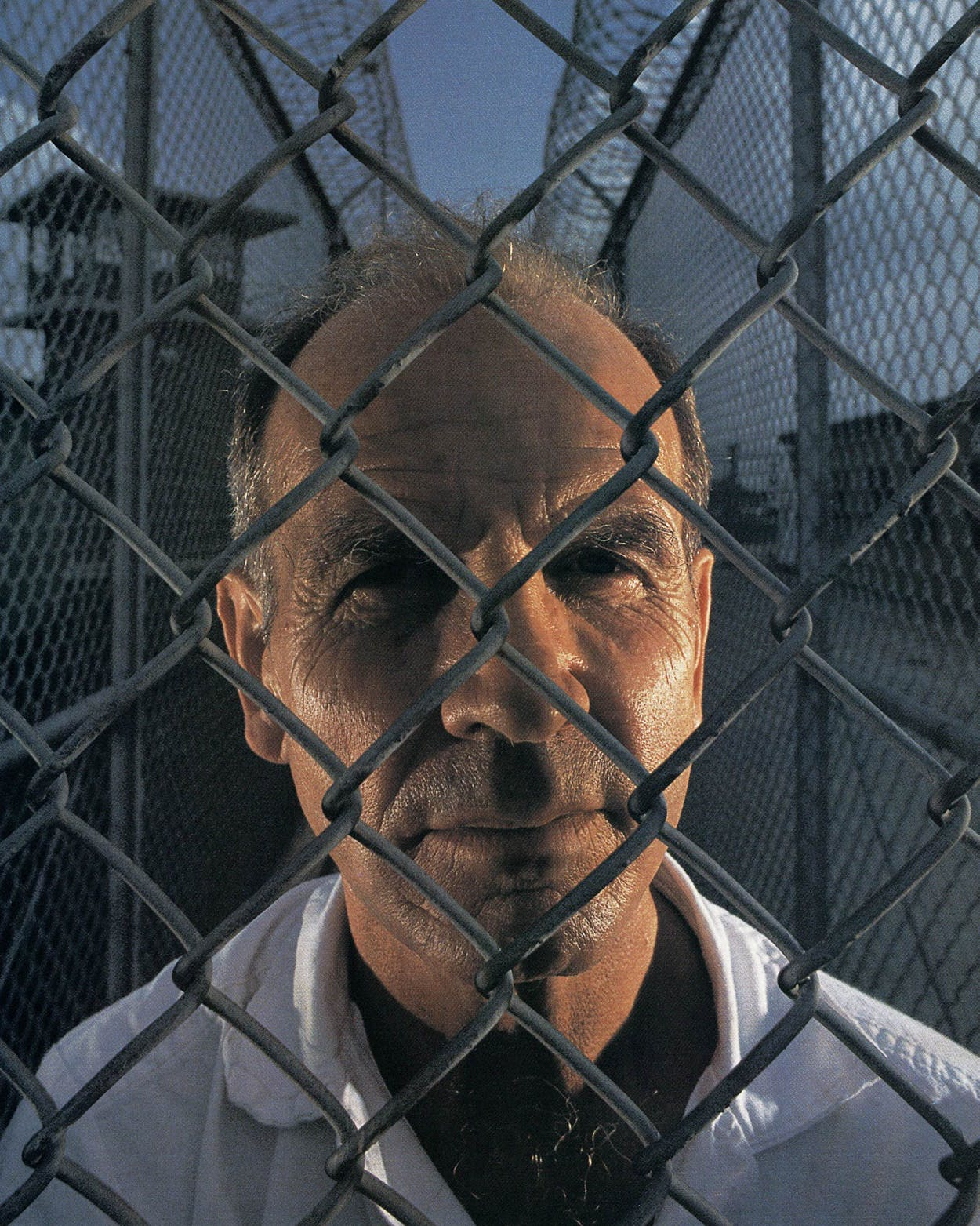 Howard Pharr looks through a chain link fence at prison.